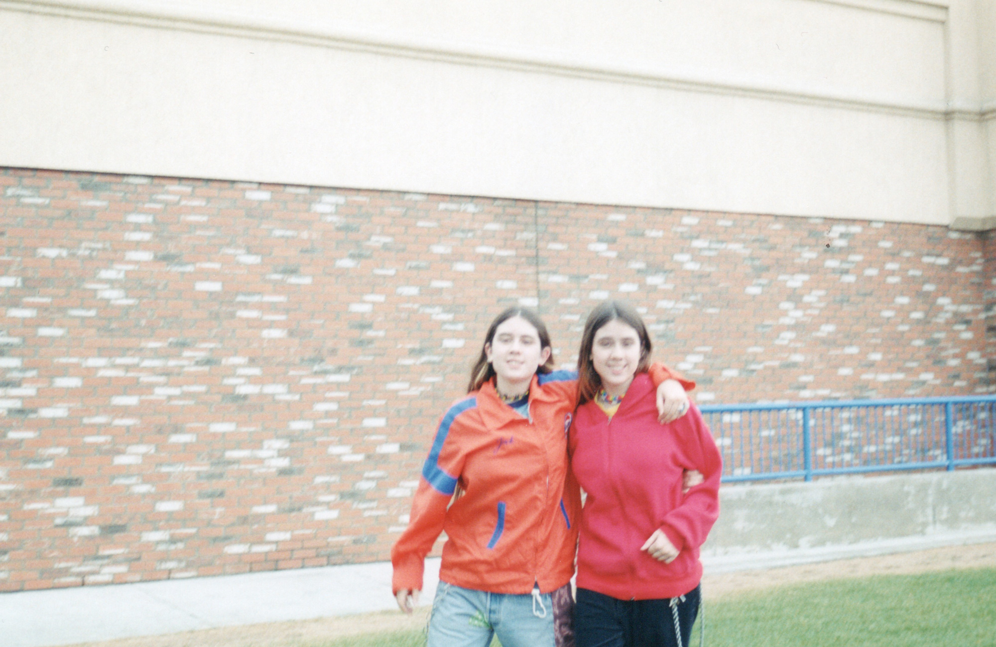 Tegan and Sara in front of a high school