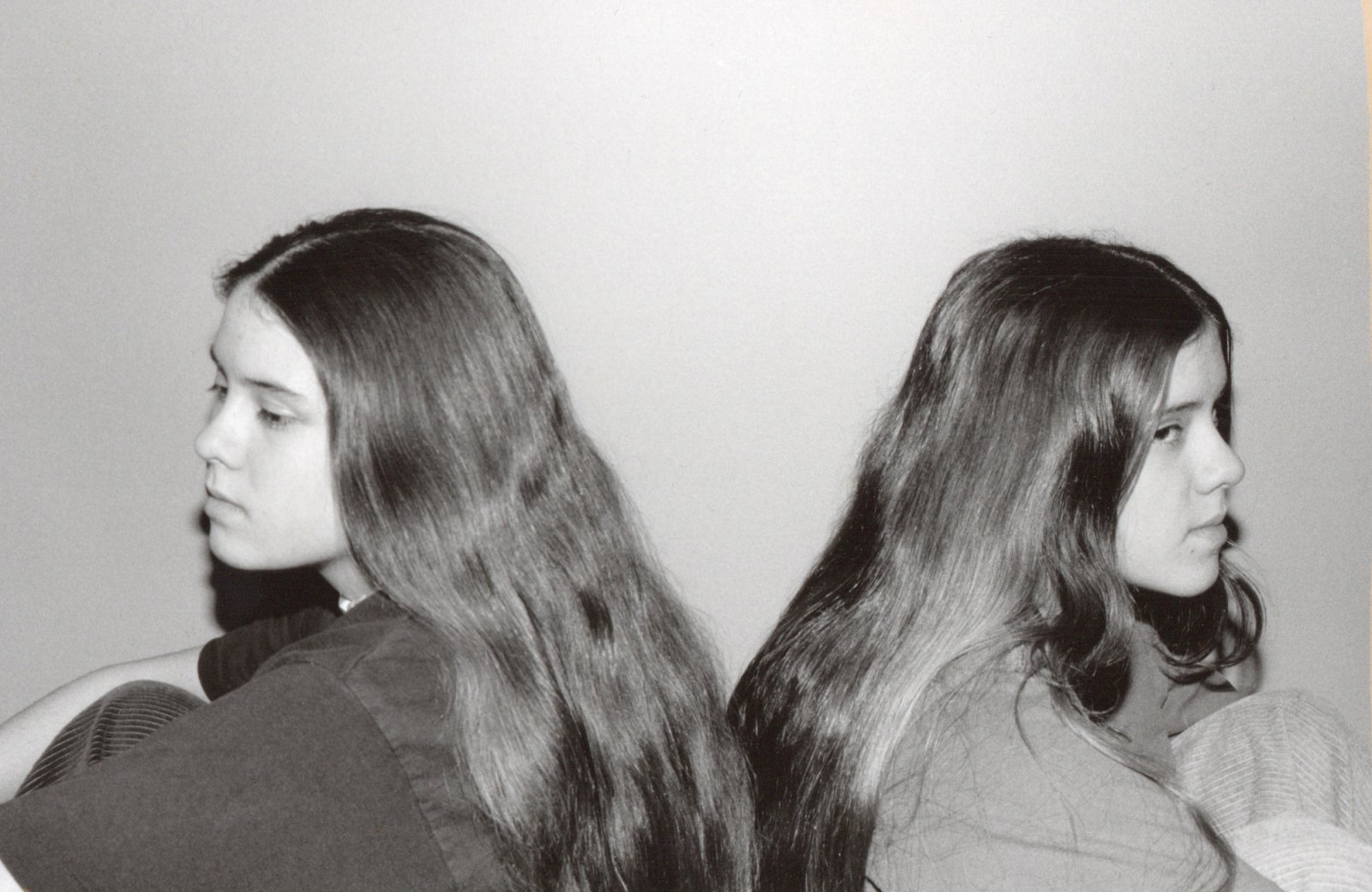Black and white photo of high school Tegan and Sara sitting back-to-back